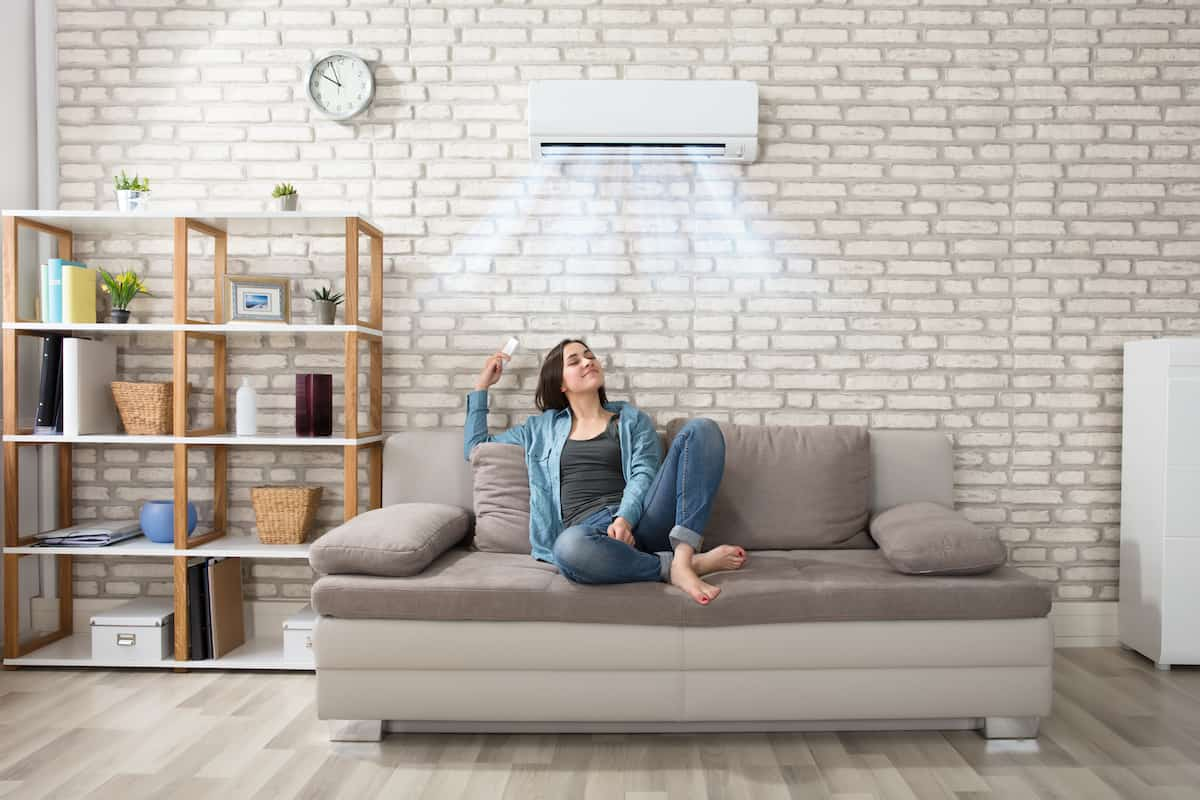Happy woman holding a remote under an air conditioning unit